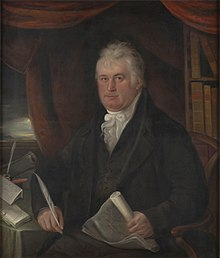 An image of Thomas Coke, Edward Coke's descendant. He is seated at a table with a pen in one hand and a scroll in the other. There are bookshelves in the background.