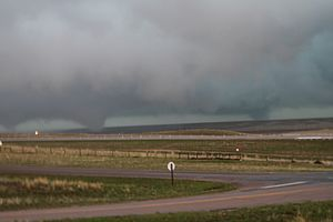 Slightly elevated photograph of three tornadoes: one at center-left, one at center, and one at center-right.