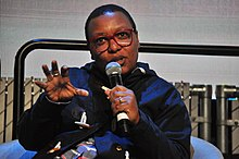 Meshell Ndegeocello speaking holding a mic in her left hand.