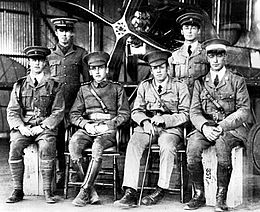 Six men in military uniforms with peaked caps, two standing and four seated, in front of a biplane