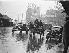 A dray, a Ford and a Morris Oxford Roadster, both 1932 models, in summer rain, Railway Square, Sydney, Jan 1935 - by Sam Hood (3293866395).jpg