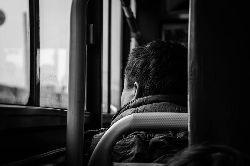File:A man on the bus watching the scene on the street.jpg