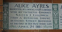 "A tablet formed of six standard sized tiles, bordered by green flowers in the style of the Arts and Crafts movement. The tablet reads ""Alice Ayres, daughter of a bricklayer's labourer who by intrepid conduct saved 3 children from a burning house in Union Street, Borough, at the cost of her own young life April 24, 1885""."