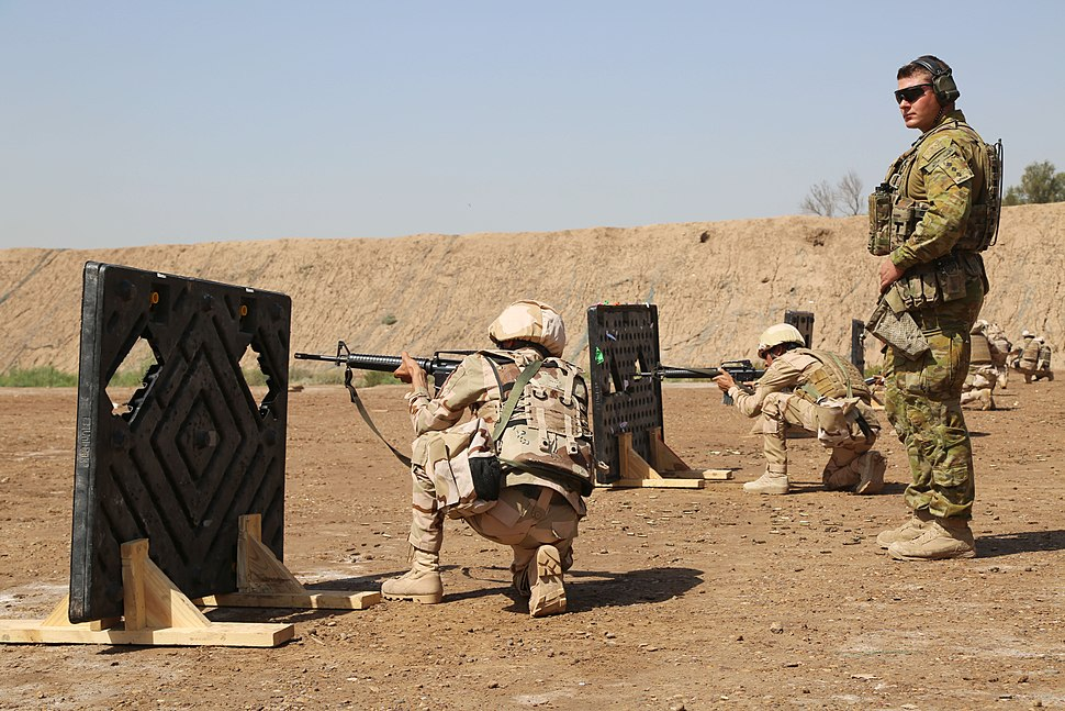 An Australian trainer with Task Group Taji, observes Iraqi soldiers as they fire their M16 rifles during aperture range training