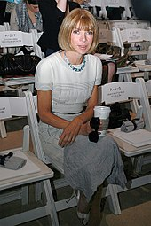 A seated woman wearing a white dress, holding a coffee cup and sunglasses, looking at the camera. The surrounding seats are empty.