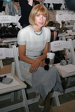 Anna Wintour wearing a white dress and holding her sunglasses and a Starbucks coffee cup in her lap at the fall 2007 Anne Klein show