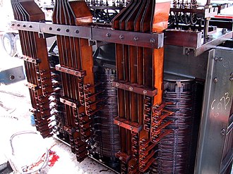"""Transformer types - In an electric arc furnace, the transformer has a heavy copper bus for the low voltage winding, which can be rated for tens of thousands of amperes. Winding beginnings and ends are led out separately and """"interleaved"""" for the external delta closure in a Knapsack connection. The transformers are immersed in oil for cooling and insulation, and are designed to withstand frequent short circuits."""