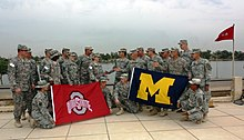 "Two groups of soldiers in camouflage uniforms staring at each other on a waterfront; the left group carries a red flag with a silver ""O"" and the words ""OHIO STATE"" on it; the right group carries a blue flag with a yellow ""M"" on it."