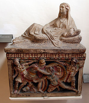 Auxilia - Etruscan funerary urn crowned with the sculpture of a woman and a front-panel relief showing two warriors fighting, polychrome terracotta, c. 150 BC