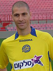 A upper-body photograph of bald white man, wearing a yellow association football shirt.