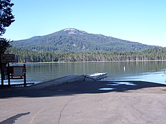 A parking lot with a forest-lined lake behind it, and a gentle sloping mountain in the background