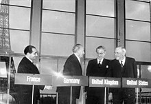 Four men stand behind podiums with their country names of France, Germany, United Kingdom, and United States, in front of a backdrop of the Eiffel Tower.
