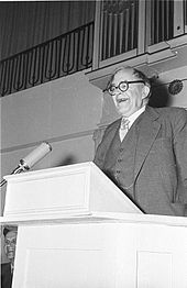 black and white photo of Barth laughing while speaking standing at a podium