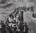 COLLECTIE TROPENMUSEUM Bevolking en een groep krijgers in vol ornaat bij de stenen tafels op het dorpsplein tijdens een burgerschapsfeest te Bawomataloewo op Nias TMnr 60042393.jpg
