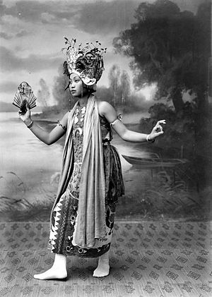Gandrung - A Gandrung dancer with traditional costume, a fan and a shawl in a dance movement.