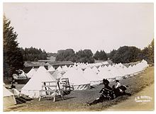 Rows of circular tents on an open grass field in Golden Gate Park, 1906