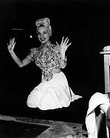 Ridetanta Miranda, en kostumo, tenas supren she manojn post postlasado de she presaĵoj ekster la ĉina teatro de Grauman.