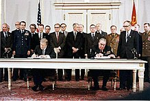 Carter and Brezhnev sitting next to each other.