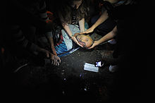 Civilians assist an injured man.