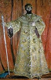 Un hombre corpulento que vestía una túnica bordada en oro y una corona, que llevaba un gran bastón.