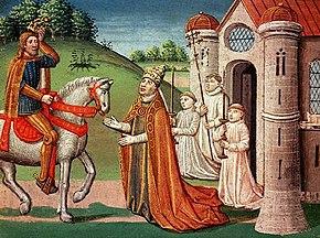 Un homme barbu chevauche un cheval blanc qui paraît assez petit, avec une tête très fine. Il fait face à trois hommes d'Église, devant une église.