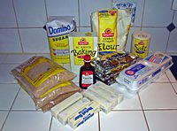 An arrangement consisting bags of brown sugar, white sugar, flour and chocolate chips; boxes of baking soda and salt; a carton of eggs, wrapped sticks of butter and a bottle of vanilla extract on a kitchen counter