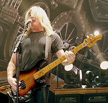 A fifty-eight-year-old man is singing into a microphone while playing a bass guitar. Behind him are stage lights and a partial view of a large steam train. His long white hair partly obscures his face. He wears a dark tee-shirt and darker pants.