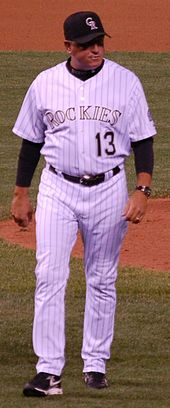 "A middle-aged man in a dark baseball cap, white pinstriped baseball uniform with ""ROCKIES 13"" on the chest, and a black shirt underneath walks away from a pitchers mound."