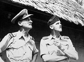 Half-length informal portrait of two men in short-sleeved tropical military uniforms with pilot's wings, standing in front of a hut and looking into the sky