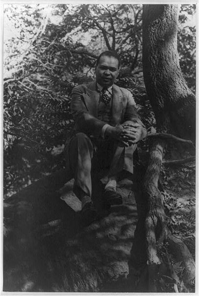 Countee Cullen in a three piece suit and tie sitting on a rock next to a tree in Central Park with foliage behind him. His fingers are intertwined to hold his left knee and he is looking at the camera.