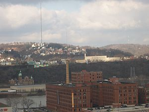 Spring Hill (background, with radio mast), as seen from Frank Curto Park. The Cork Factory lofts in the Strip District and Troy Hill are located in the foreground.