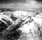 Dawes Glacier, tidewater glacier with banded ogives and hanging glaciers on the mountainside, August 29, 1971 (GLACIERS 5396).jpg