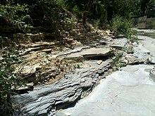 This photo shows a bluish layer of claystone below a greyish slab and a layer of yellow and brown above that. Where this more impervious rock forms the bottom of the creek, there is flowing water all year.