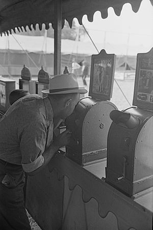 Peep show - A man peers into the viewer of a peepshow at a State Fair in 1938