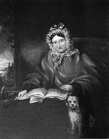 Half-length portrait of a woman wearing a frilly cap. She is in bed, with a book, her glasses, and her dog.