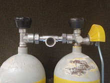 The top of a twin set of steel 7-litre cylinders shows a pair of Dräger vertical spindle taper thread valves with rubber knobs and DIN outlets linked by a single DIN centre-outlet manifold. The left side cylinder has a reserve lever with operating rod and a yellow plastic guard over the lever to reduce the risk of it being inadvertently opened by bumping against the surroundings.