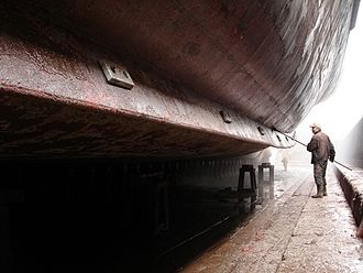 Anti-fouling paint - Ship hull being cleaned of fouling in drydock