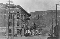 A partial black-and-white view of the Wheeler from a slightly different angle than that shown in the article's lead photograph, looking down the street towards a mountain in the distance. Telephone poles and wires run along both sides, and a small electric light is suspended above the intersection.