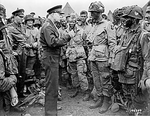 101st Airborne Division - General Dwight D. Eisenhower speaking with 1st Lieutenant Wallace C. Strobel and men of Company E, 502nd Parachute Infantry Regiment on 5 June. The placard around Strobel's neck indicates he is the jumpmaster for chalk No. 23 of the 438th TCG.