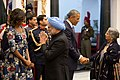 First Lady Michelle Obama greets former Indian Prime Minister Manmohan Singh as President Barack Obama greets his wife Gursharan Kaur prior to the State Dinner at Rashtrapati Bhavan.jpg