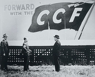 Saskatchewan general election, 1944 - Tommy Douglas standing under a Co-operative Commonwealth Federation election billboard with C.M. Fines and Clarence Gillis shortly after the historic 1944 election that swept the Saskatchewan CCF to power.