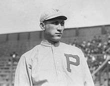 "A black-and-white image of a man wearing an old-style baseball uniform with a ""P"" on the chest and a white crownless baseball cap"