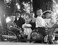 Gruppbild, familjebild. Man och kvinna med fyra barn poserar runt leksakshäst med vagn i park - Nordiska Museet - NMA.0052055.jpg