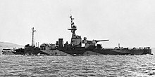 A small warship with one large gun turret sits off shore. The vessel is painted with an angular camouflage scheme of alternating light and dark colors