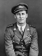 Half length portrait of man in military uniform with peaked cap and pilot's wings on left breast pocket