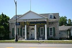 "A light brown stone building with a pointed roof, green shutters and white columns on the front. In front of it are a sidewalk, a blue marker with gold writing, and a portion of street. Black letters above the front columns read ""Holland Land Office Museum"", which is also on a banner across the front."
