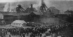 Black and white photograph of the Universal Colliery, taken from a raised position, and showing crowds waiting for news