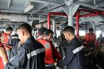 Indian Navy officers help evacuees put on their life jackets.JPG