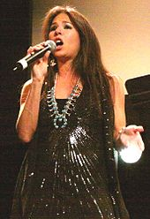 A woman holding a microphone and wearing a black dress with sequins and a necklace