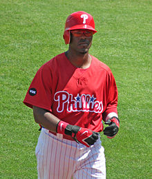 A dark-skinned man in a red baseball jersey, white baseball pants with red pinstripes, and a red batting helmet walks on a baseball field while taking off his black and red batting gloves.